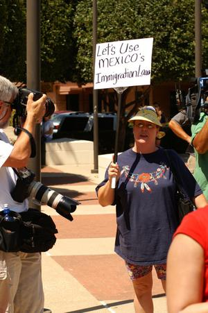 "Primary view of object titled '[Protester with anti-immigration sign, ""Let's use Mexico's immigration law""]'."