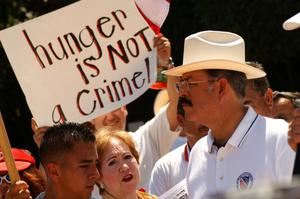 "[Protesters with sign, ""Hunger is not a crime""]"