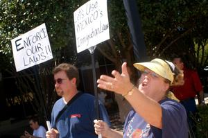 Primary view of object titled '[Two protesters holding signs with anti-immigration messages]'.