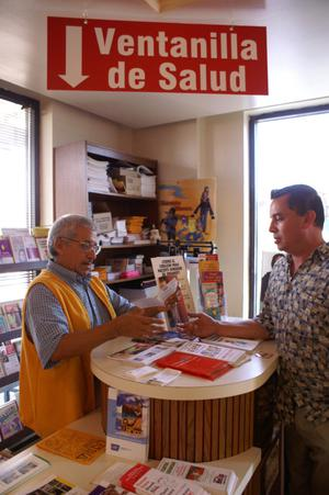 Employee from Ventanilla de Salud assists a visitor from behind a counter, Health: Ventanilla de Salud