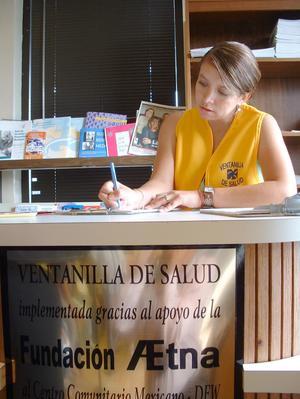 Employee from Ventanilla de Salud working behind the entrance counter, Health: Ventanilla de Salud