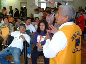 Primary view of object titled '[Employee from Ventanilla de Salud addresses the waiting room crowd]'.
