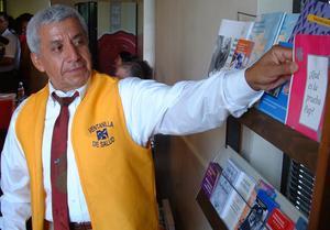 Employee from Ventanilla de Salud reaches for Spanish-language medical brochures, Health: Ventanilla de Salud