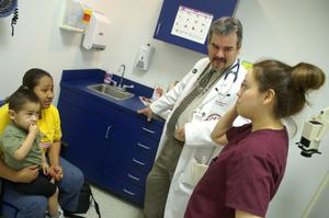 [Dr. Henry Lenk speaks with clinic staff member as mother and child wait]