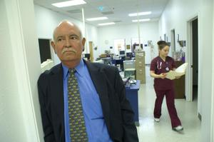 Primary view of object titled '[Eddy Herrera leans against doorway with clinic staff member in the background]'.