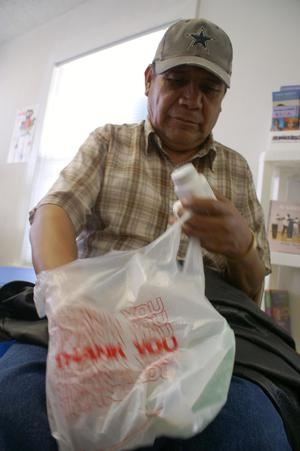 Primary view of object titled '[Man with plastic grocery bag and medicine]'.