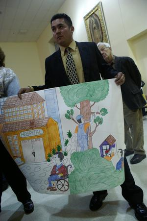 Primary view of object titled '[Sigifredo Munoz holds a large drawing in his hands]'.