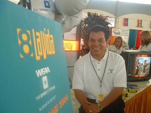 Primary view of object titled '[John Rios smiling at this display booth]'.