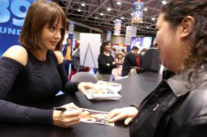 Primary view of object titled '[A woman smiles while Gabriela Spanic gives her an autograph]'.