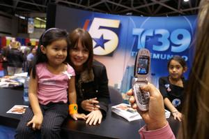Primary view of object titled '[Photo of Gabriela and young fan being taken with a cellphone]'.