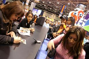 [Gabriela gives her autograph to her fans]
