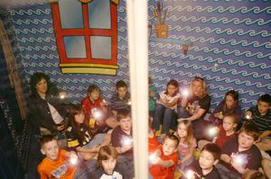 [Teachers and students point flashlights at possible dangers in a home safety demonstration]