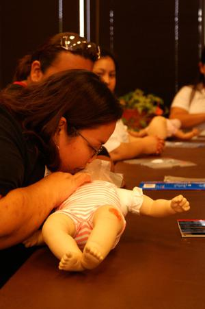 Primary view of object titled '[Mother practices first aid during an Early Education Program class]'.