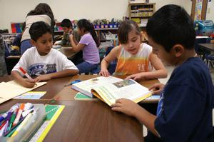 Primary view of object titled '[Students share a text book at Crockett Elementary]'.