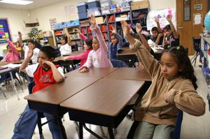 Primary view of object titled '[Students raise their hands in a Crockett Elementary class]'.