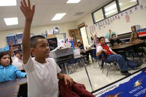 Primary view of object titled '[Students Raising Their Hands in a Class at Crockett Elementary]'.
