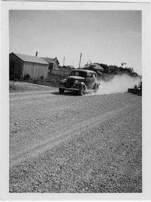 [U.S. Highway 79 Car traveling on untreated gravel]