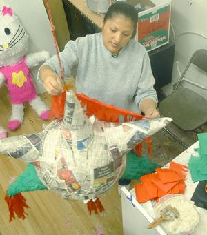 Primary view of object titled '[Woman decorates a piñata]'.