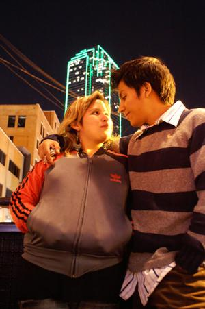 Primary view of object titled '[Young man with arm around woman, building with green lights in background]'.