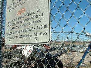 Primary view of object titled '[Sign posted on chain link fence]'.