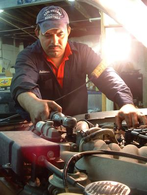 Man Working Under The Hood Of A Motor Vehicle The