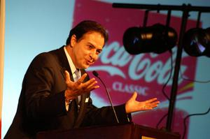 "Primary view of object titled '[Man speaking at podium with ""Coca Cola"" sign in background]'."