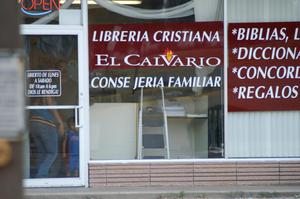 Primary view of object titled '[Glass facade of Christian bookstore with Spanish signage]'.