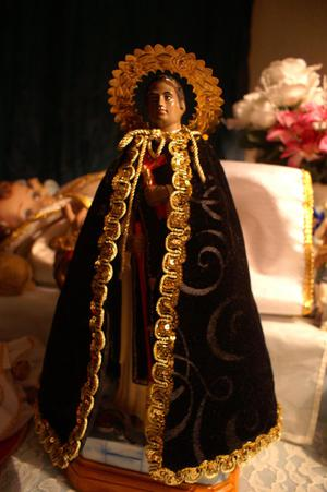 Primary view of object titled '[Figure of St. Martin de Porres in dark robe with gold trim]'.