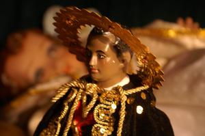 [Figure of St. Martin de Porres with blurred image in background]