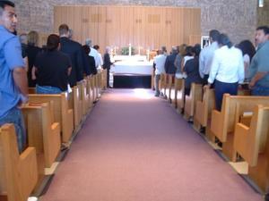 Mourners standing in rows of pews, Edgar Vera