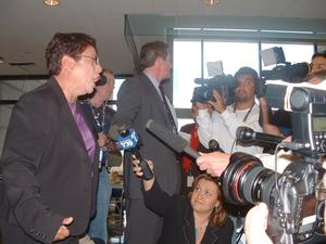 Primary view of object titled '[Woman speaking to media people with microphones and cameras]'.