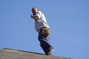 [Man standing on roof and talking on cellular phone]
