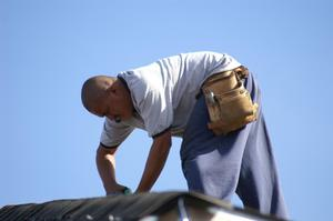 Primary view of object titled '[Man bent over and working on roof]'.