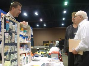 [Man and woman talking to man with display of medical supplies]