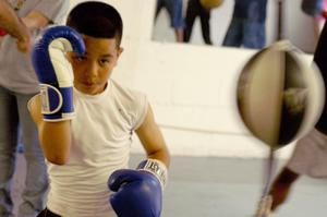 Primary view of object titled '[Boy in blue and white boxing gloves]'.