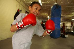 Primary view of object titled '[Boy in red boxing gloves in front of blue heavy bag]'.