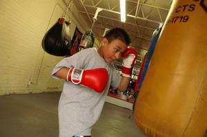 Primary view of object titled '[Boy in red boxing gloves surrounded by practice bags]'.
