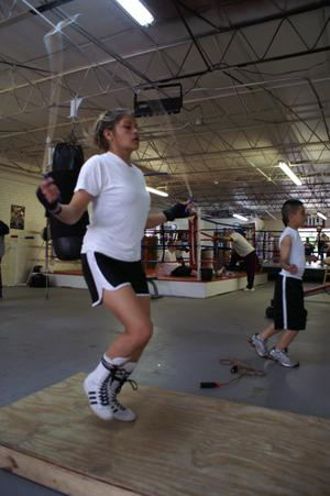 Primary view of object titled '[Young woman and boy jumping rope in boxing gym]'.