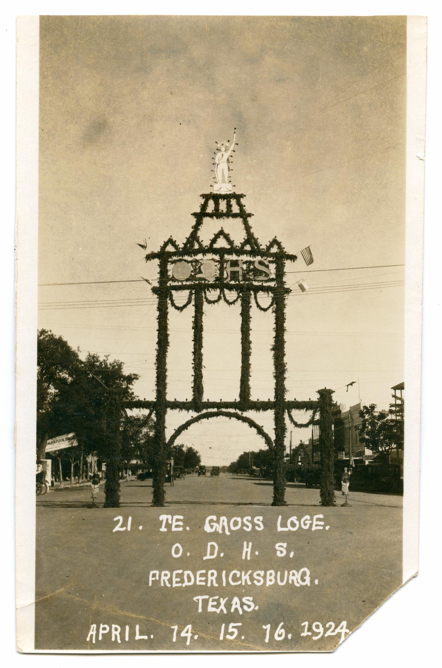 """[Photograph of the O. D. H. S. Archway in Fredericksburg], Photograph of the O. D. H. S. decorative archway in Fredericksburg. The archway has a man on top and the letters O D H S on it, and it is covered in garland and lights. The following is printed in white at the bottom: """"21. TE. Gross Loge. O. D. H. S. Fredericksburg, Texas. April. 14, 15, 16, 1924."""" The following stamp appears on the back: """"Welgehausens Kodak Finishing, Enlarging Fredericksburg, Tex."""","""