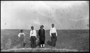 [Photograph of a Boy, two Men, and a Woman]