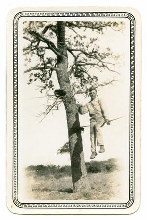 Primary view of object titled '[Photograph of a Man Sitting on a Rope Tied to a Tree]'.