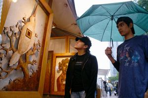 Primary view of object titled '[Two young people looking at artwork, standing under umbrella]'.