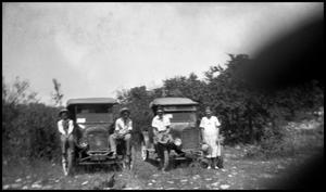 Primary view of object titled '[Photograph of a Family Sitting on Automobiles]'.