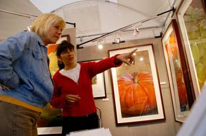 Primary view of object titled '[Two women looking at artwork, one pointing with her left hand]'.