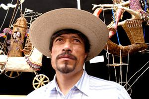 Primary view of object titled '[Man in straw hat gazing upward with craft items hanging in background]'.