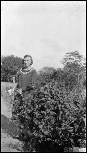 Primary view of object titled '[Photograph of Ana Jentsch next to a Bush]'.