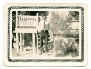 Primary view of object titled '[Photograph of  Young Man Standing on the Steps of a Porch]'.