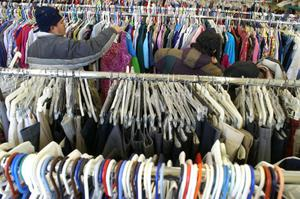 Primary view of object titled '[People search for the clothing they need at Dallas Catholic Charities]'.