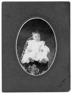[Portrait of unidentified baby in white dress and white shoes]