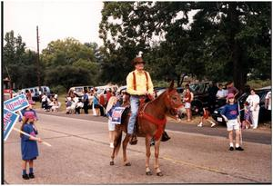 Primary view of object titled '[Charles Wilson Rides a Donkey in the 1994 Diboll Day Parade'.